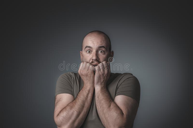 Portrait of caucasian man with scared expression bringing his hands to his face royalty free stock images