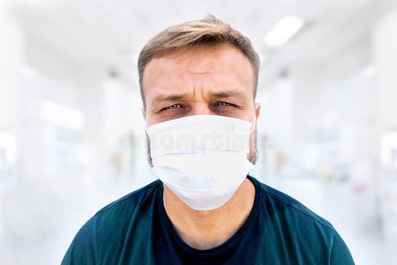 Portrait of caucasian white male doctor, millennial, in medical surgeon face mask and sweaty short. Coronavirus outbreak, medical personal fatigue and stock image