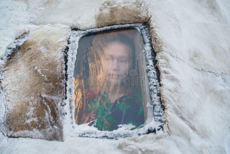 Portrait of caucasian woman through frozen window of Siberian yurt. stock image
