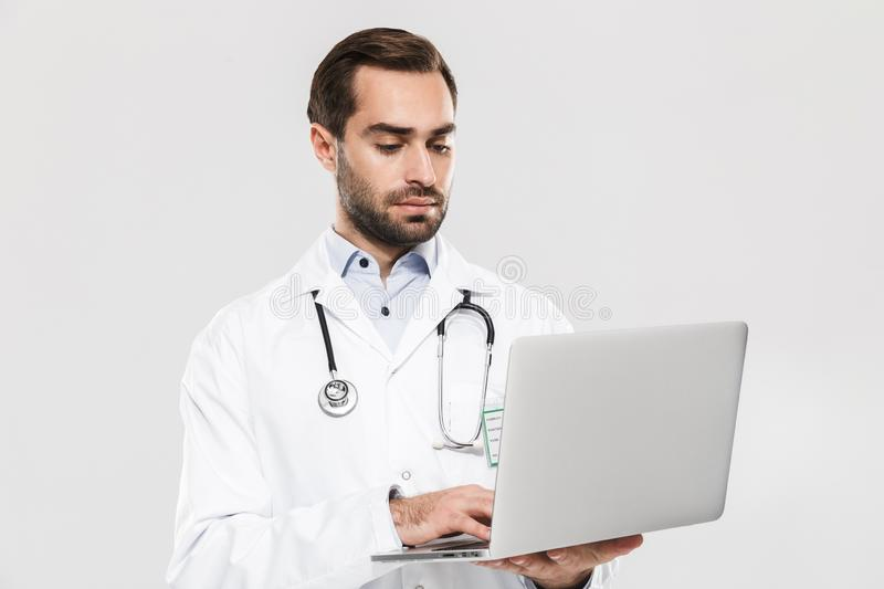 Portrait of caucasian young medical doctor with stethoscope working in clinic and holding laptop stock photography