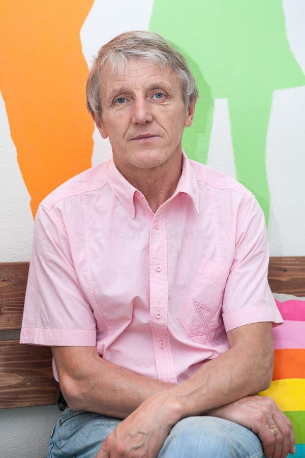 Portrait caucasien supérieur d'homme Une personne dans la chemise à manches courtes rose, se reposer d'intérieur, regardant l'app photos stock
