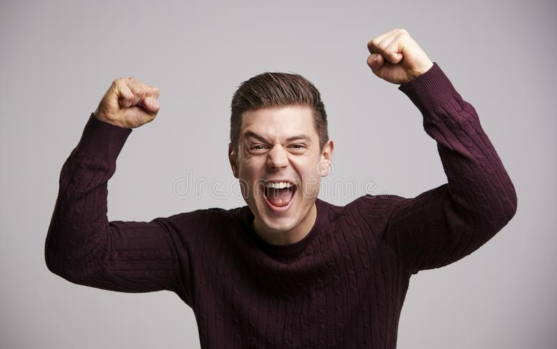 Portrait of a celebrating young white man with arms up royalty free stock photos