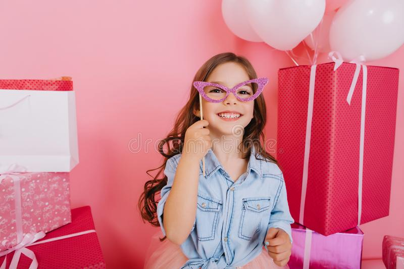 Portrait celebration happy birthday party of amazing excited little girl in blue shirt holding purple mask on face. Expressing positivity to camera of child royalty free stock photos