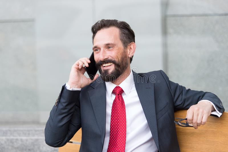 Portrait of charismatic delighted businessman talking on mobile phone outdoors royalty free stock photography