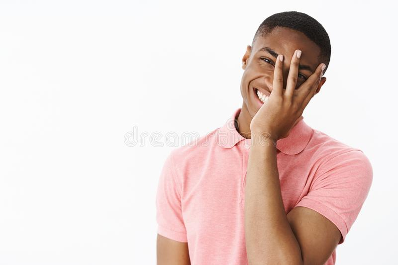 Portrait of charismatic happy good-looking bright african american guy holding palm on face peeking through fingers stock images