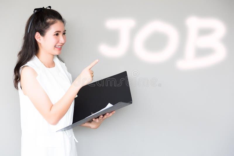Portrait charmant la belle femme d'apprenti : La fille attirante tient le fichier document et dirige son doigt pour copier l'espa image libre de droits