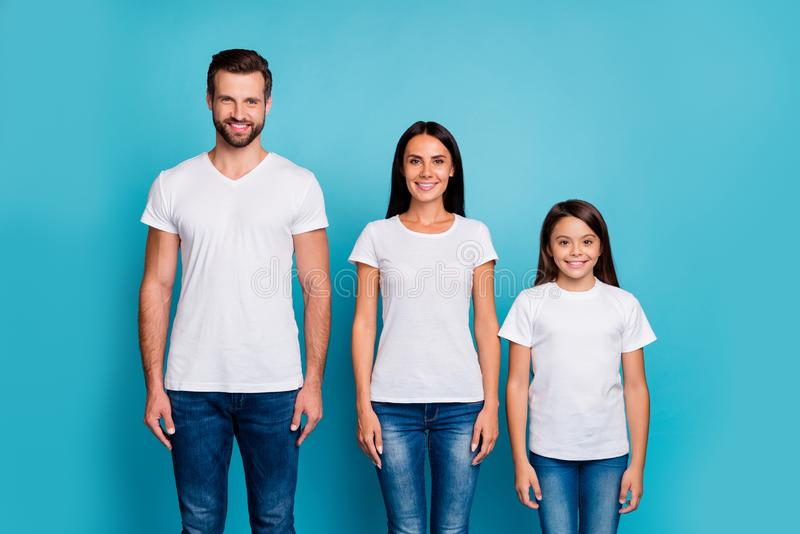 Portrait of charming adults and schoolkid standing with beaming smile wearing white t-shirt denim jeans isolated over royalty free stock photography
