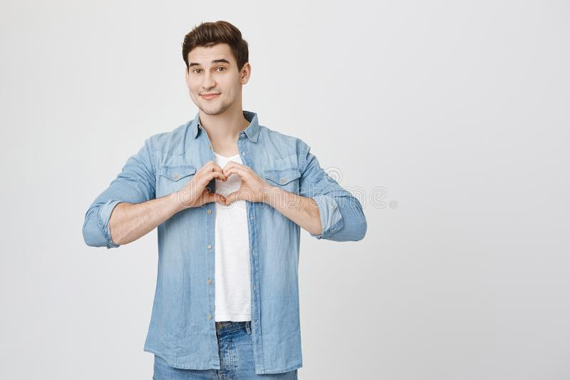 Portrait of charming attractive european student, holding hands in heart gesture and lifting eyebrows while smiling stock photo