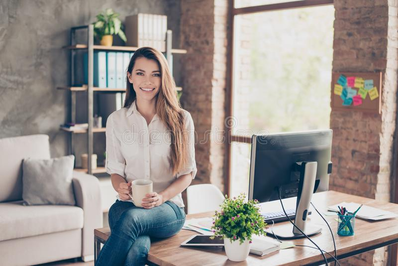 Portrait of charming attractive stunning pretty lovely cute expert freelancer with long hair toothy beaming smile relaxing on. Desktop with cup of aromatic royalty free stock photo