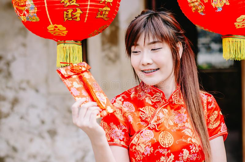 Portrait charming beautiful asian woman wear cheongsam dress gets red envelopes from her family. Pretty girl shows red envelopes.P royalty free stock image
