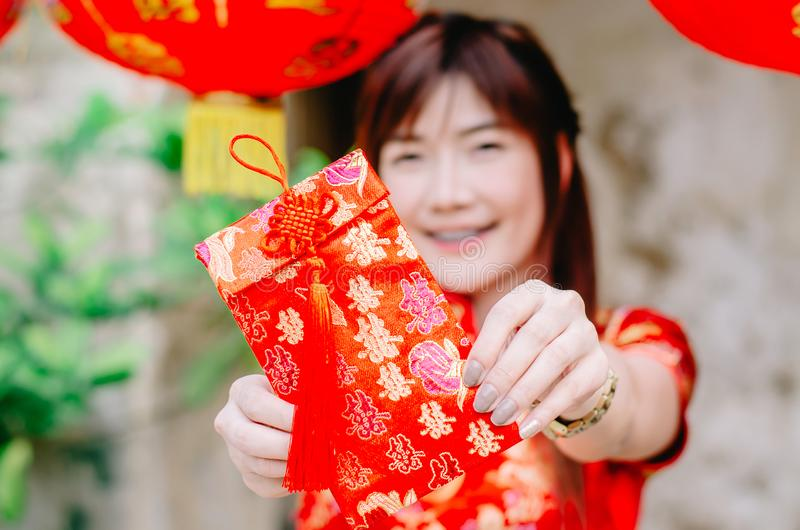 Portrait charming beautiful asian woman wear cheongsam dress up holding red envelop to the camera, The symbol of Chinese New Year. stock photo