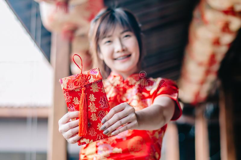 Portrait charming beautiful asian woman wear cheongsam dress up holding red envelop to the camera, The symbol of Chinese New Year. Select focus red envelop stock image