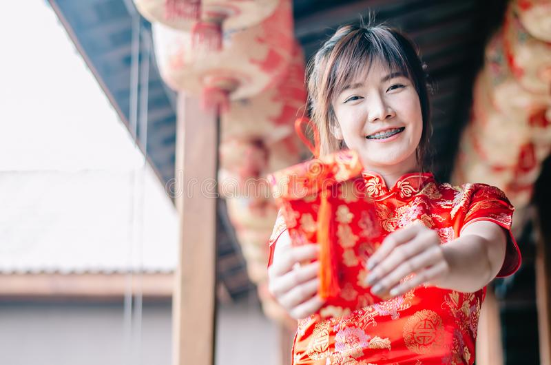 Portrait charming beautiful asian woman wear cheongsam dress up holding red envelop to the camera, The symbol of Chinese New Year. Select focus asian woman stock photos