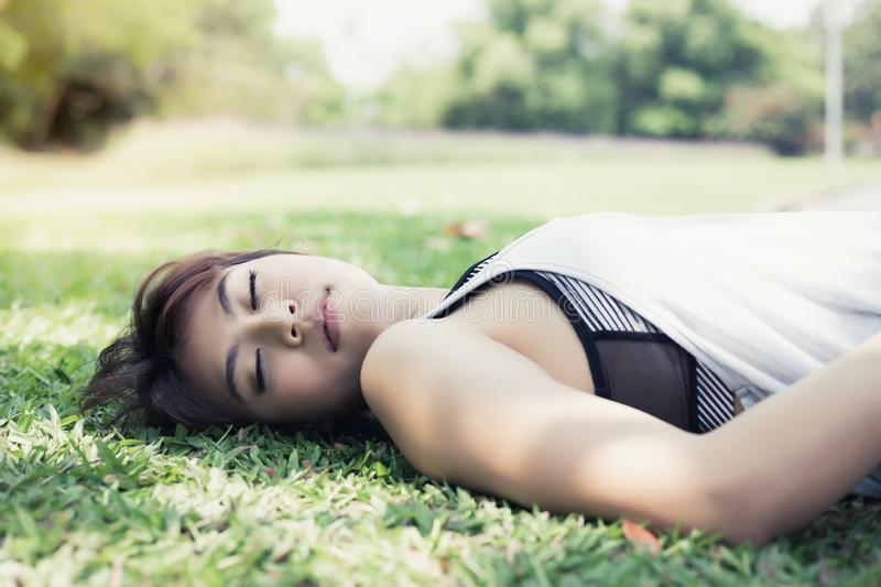 Portrait charming beautiful fainted or unconscious woman. Attractive girl is falling down on garden while she is exercising. royalty free stock images