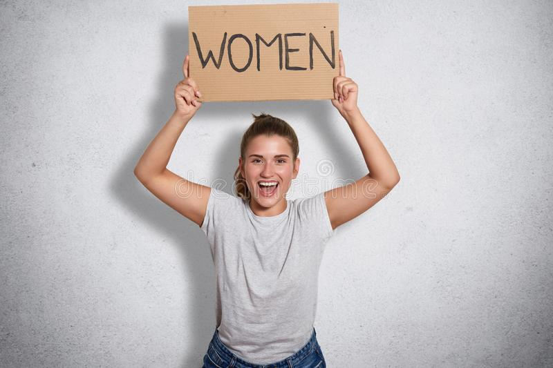 Portrait of charming beautiful feminist opening her mouth widely with happiness, raising arms, showing inscription women, calling. For support and unity for stock photo