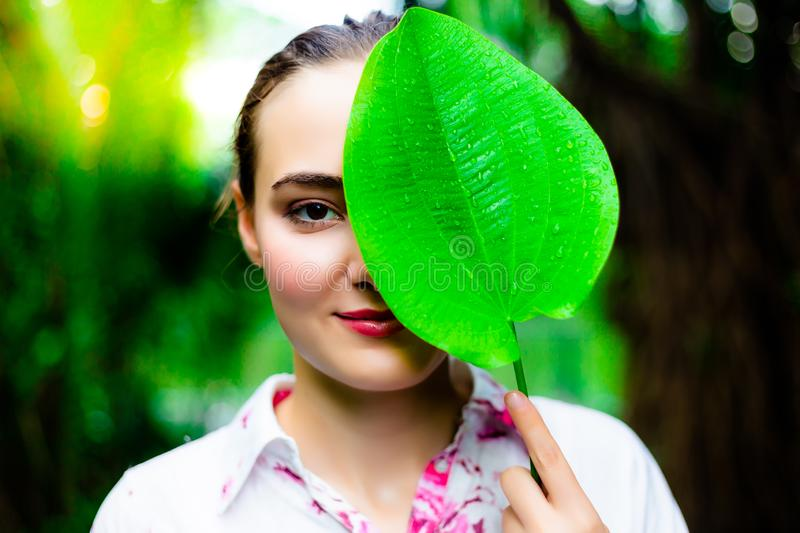 Portrait charming beautiful woman. Attractive woman holds a green leaf close her half face. Gorgeous girl compare her face and le stock photos