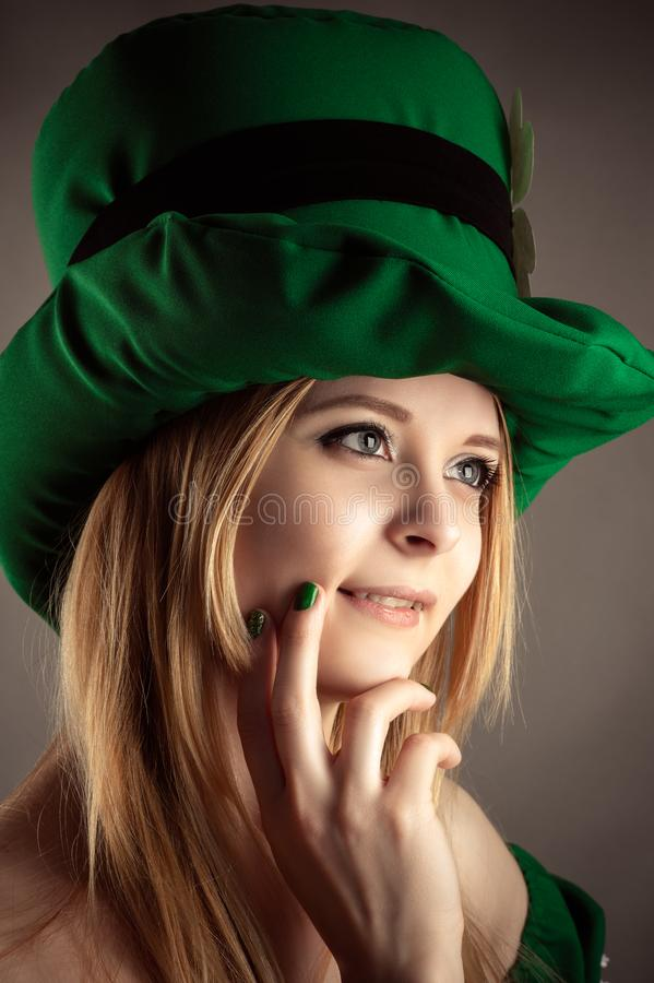 Portrait charming blond girl in leprechaun hat closeup stock photography