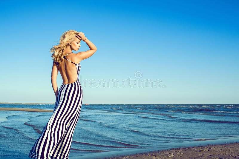 Portrait of charming blond long-haired woman in long black and white striped dress with naked back walking along the seaside stock photo