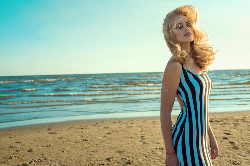 Portrait of a charming blond long-haired woman in long black and white striped dress smelling and enjoying aroma of the sea. Portrait of a charming blond long stock photos