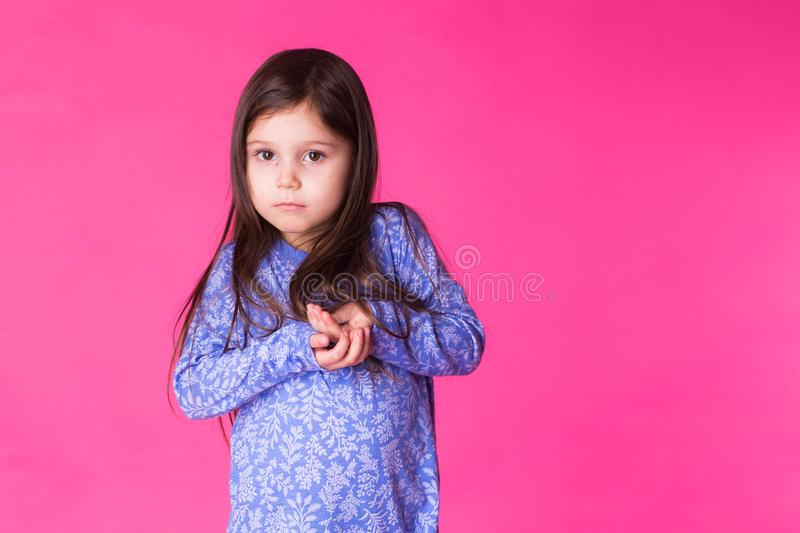 Portrait of a charming brunette little child girl, isolated on pink background stock photos