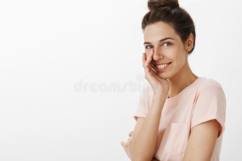 Portrait of charming charismatic european woman with combed hair standing right side of copy space touching face as. Giggling flirty and smiling sincere at stock images