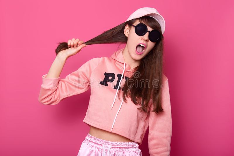 Portrait of charming dark haired female in pink hoodie, cap and suglasses, holding pulling hair, looking at camera with opened royalty free stock image