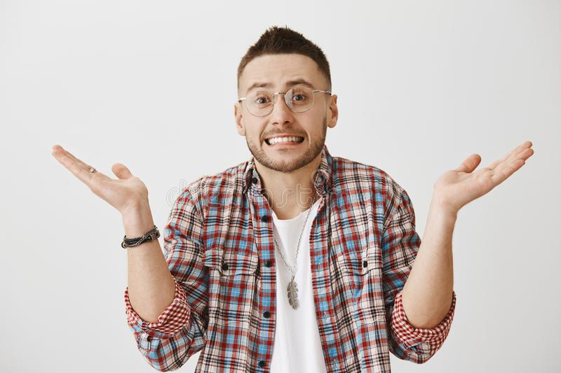 Portrait of charming european male model in glasses shrugging and showing teeth while standing with spread raised palms. Feeling shame or being guilty, saying stock photos