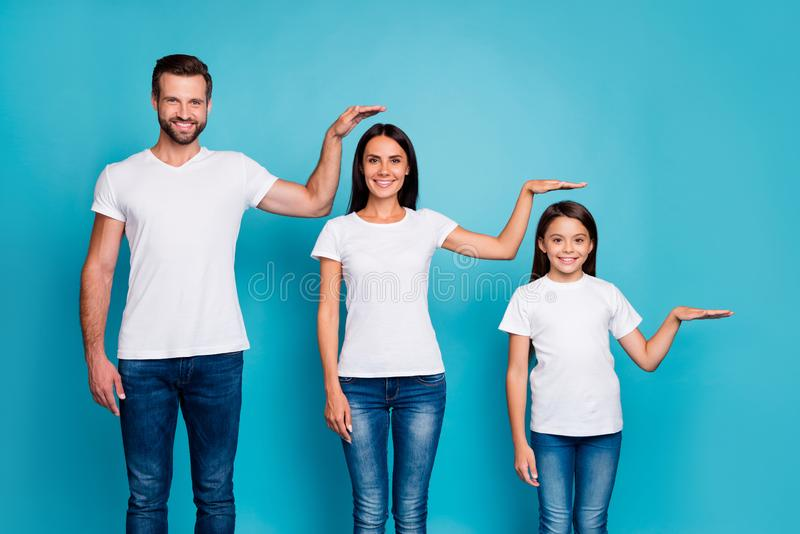 Portrait of charming family holding palm wearing white t-shirt denim jeans isolated over blue background royalty free stock photography
