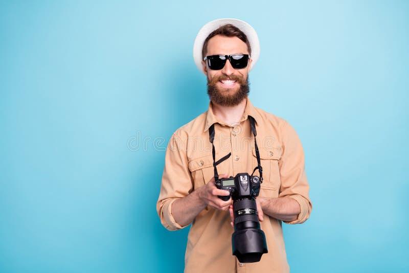 Portrait of charming guy holding camera wearing brown shirt eyeglasses eyewear  over blue background royalty free stock photo