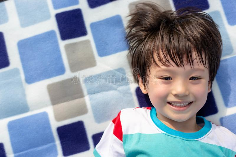 Portrait charming handsome little boy. Attractive handsome kid has nice smile and lovely face. Cute child lying down on picnic. Tablecloth. He is cheerful boy royalty free stock image