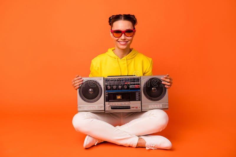 Portrait of charming lady holding boom box sitting smiling wear eyewear eyeglasses yellow sweater isolated over orange. Portrait of charming lady holding boom royalty free stock image