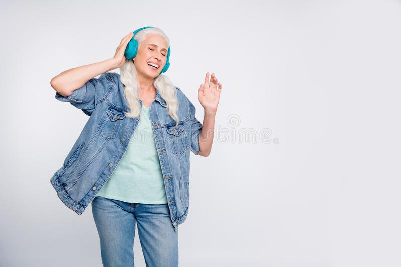 Portrait of charming lady listen soundtracks close her eyes touch electronic device isolated over white background royalty free stock image