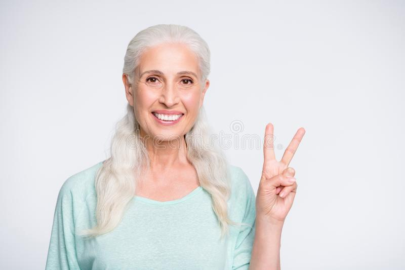 Portrait of charming lady looking ate camera smiling making v-sings isolated over white background royalty free stock images