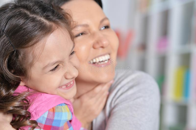 Portrait of a charming little girl hugging with mom royalty free stock photos