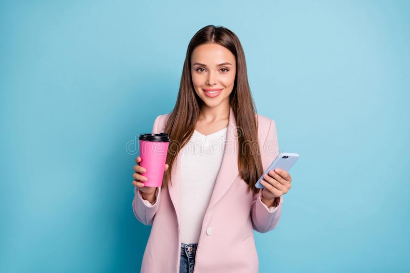Portrait of charming lovely girl using her cellphone chatting with friends holding mug wearing white t-shirt isolated stock photos