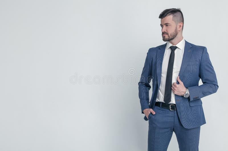 Portrait of a charming mature businessman dressed in suit posing while standing and looking at camera  over gray royalty free stock image