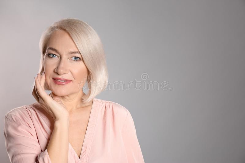 Portrait of charming mature woman with healthy beautiful face skin and natural makeup on grey background royalty free stock image