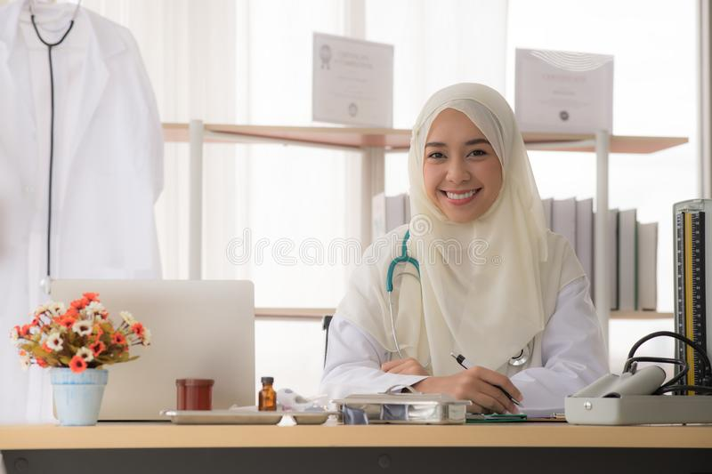 Portrait of charming muslim female doctor working at office desk and smiling at camera stock photos