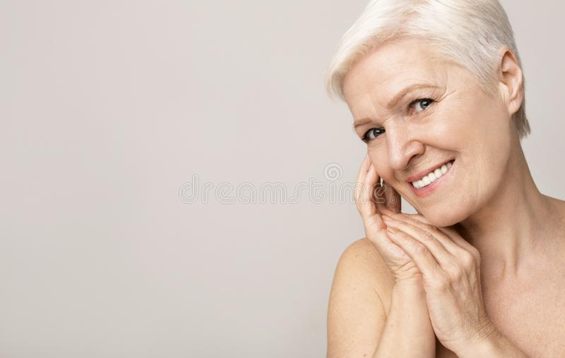 Portrait of charming nude senior woman touching her skin royalty free stock photo