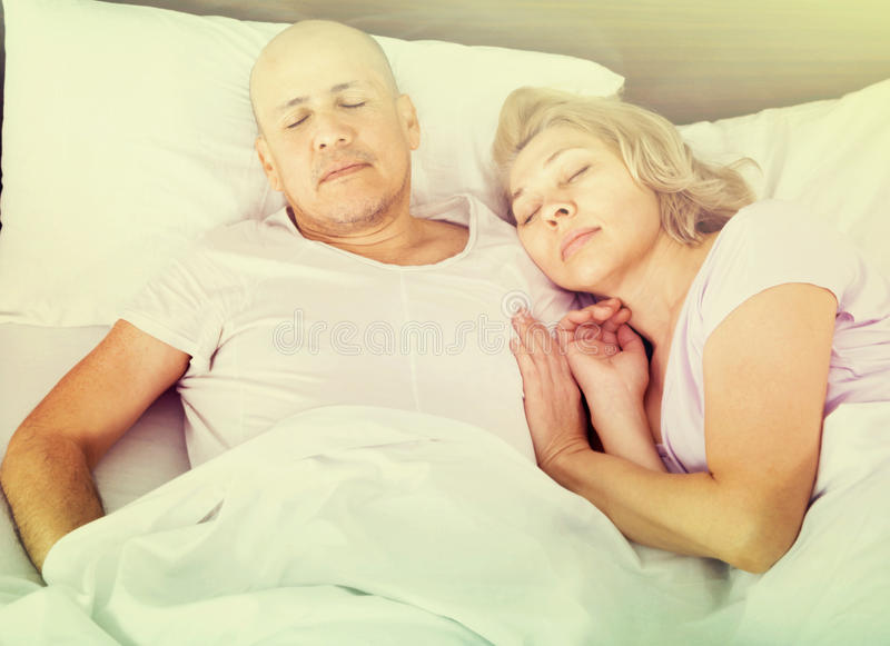 Portrait of charming ordinary mature couple napping in bed stock photos