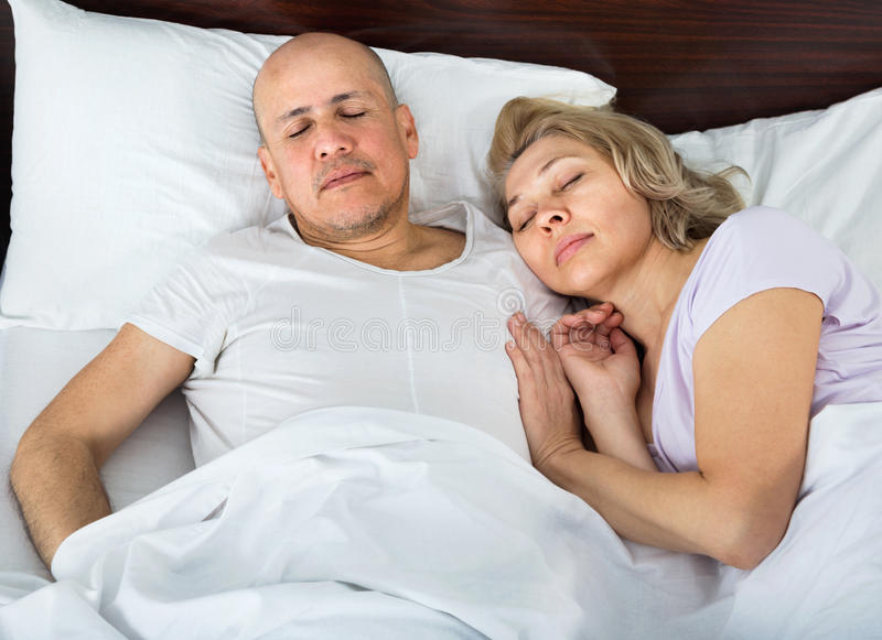 Portrait of charming ordinary mature couple napping in bed royalty free stock photo