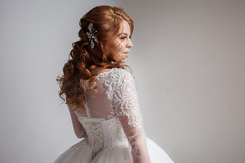 Portrait of a charming red-haired bride, Studio, close-up. Wedding hairstyle and makeup. Young woman in luxurious wedding dress royalty free stock images
