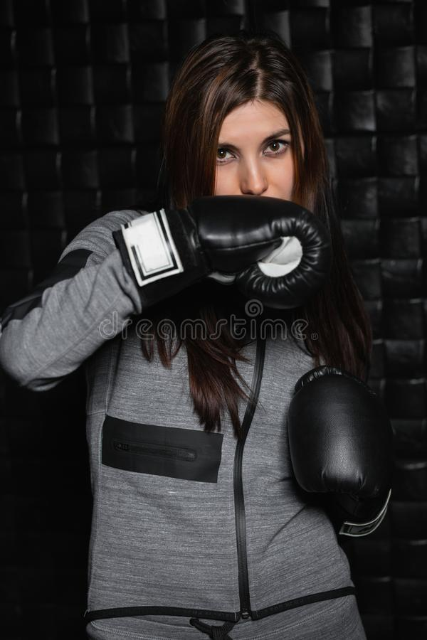 Portrait of a charming sporty brunette. With boxing gloves near the black wall stock images