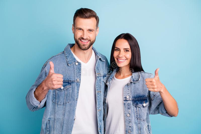 Portrait of charming spouses showing thumb up wearing denim jeans isolated over blue background stock images