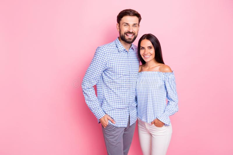 Portrait of charming sweethearts looking at camera with toothy smile isolated over pink background stock image