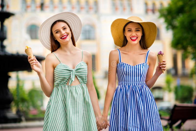 Portrait of charming women having brunette hair red pomade holding hands smiling going in town. Portrait of charming women having brunette hair red pomade royalty free stock image