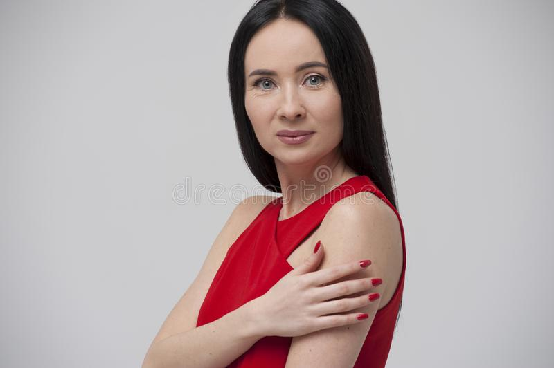 Portrait of charming young brunette woman wearing red blouse royalty free stock photo