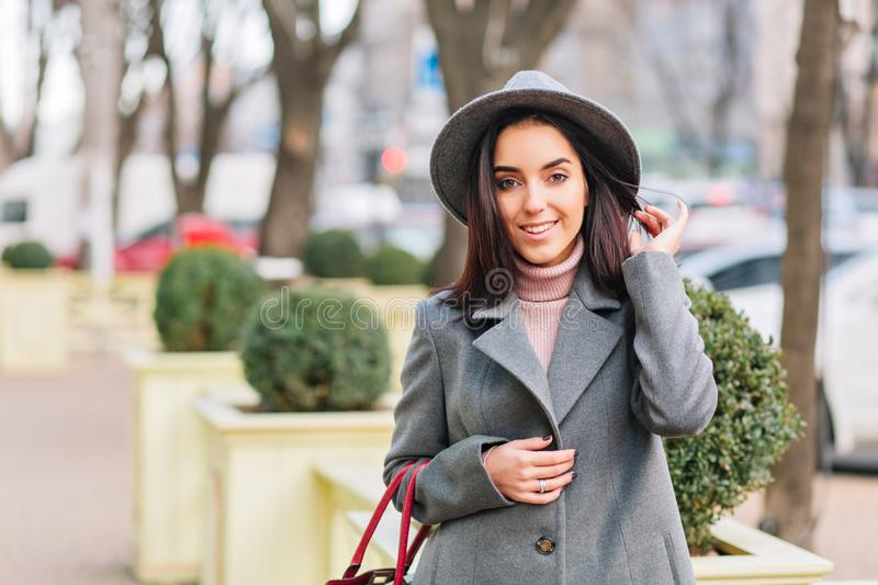 Portrait charming young fashionable woman in grey hat, coat walking on street in city park. Brunette hair, smiling to royalty free stock photos