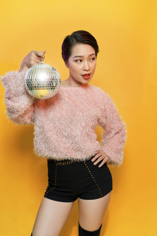 Portrait of charming young female showing tongue and fooling around holding mirror ball on head posing on yellow background. Party. And glitter fashion concept royalty free stock photo