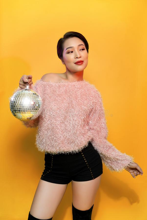 Portrait of charming young female showing tongue and fooling around holding mirror ball on head posing on yellow background. Party. And glitter fashion concept royalty free stock photography